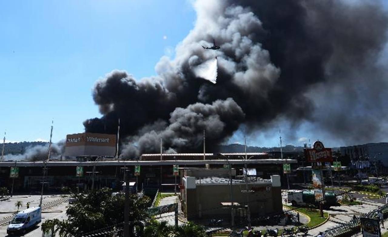 Personal de algunas tiendas afectadas por el siniestro luchaba por rescatar mercadería de las llamas. Foto EDH / César AvilésFoto EDH / Marlon Hernández