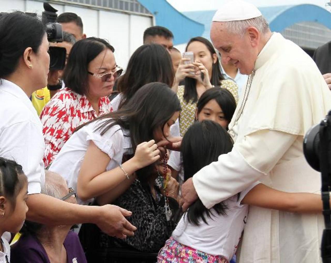 Una joven besa la mano del Pontífice, mientras unas niñas lo abraza en el aeropuerto internacional de Manila. Foto EDH /EFE
