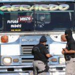 Policías recaban evidencias en el autobús en el cual fue asesinado uno de sus compañeros por supuestos miembros de pandillas que viajaban en una motocicleta. Foto EDH / Claudia Castillo.