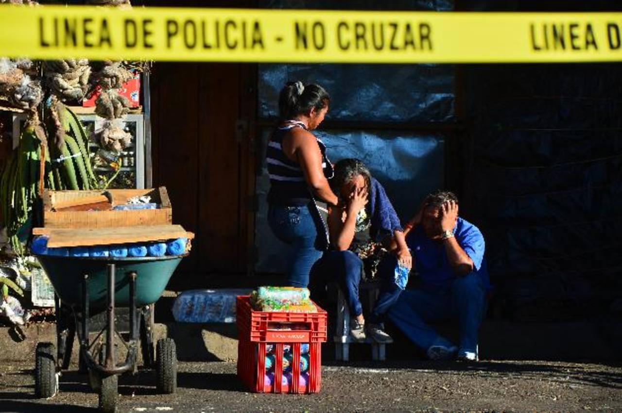Parientes de Edwin Aguilar Melara, un exconvicto, se lamentan cerca de la escena donde lo mataron, a un costado de la iglesia El Calvario, en San Salvador. Foto EDH / René Quintanilla