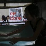 """Manifestante filipino sostiene una pancarta con la leyenda en inglés """"detengan la ejecución"""" durante un acto para pedir al gobierno indonesio que no ejecute a la filipina Mary Jane Veloso, condenada por narcotráfico."""
