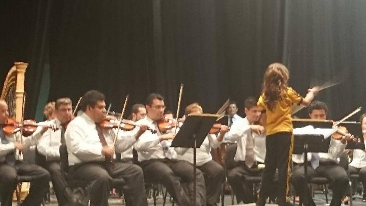 Una alumna del colegio Jerusalén, de Ilopango, dirige la orquesta durante unos minutos, ayer. Varios de los asistentes tuvieron la oportunidad de desempeñar el rol de director.