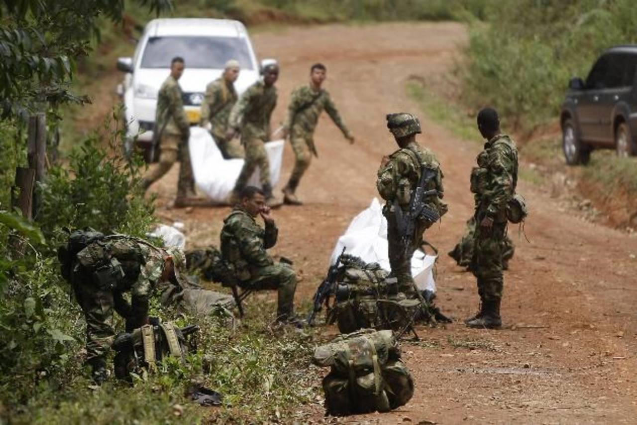 Un grupo de soldados transporta los restos de algunos de los 11 militares muertos, tras un ataque de las terroristas FARC. foto edh / efe