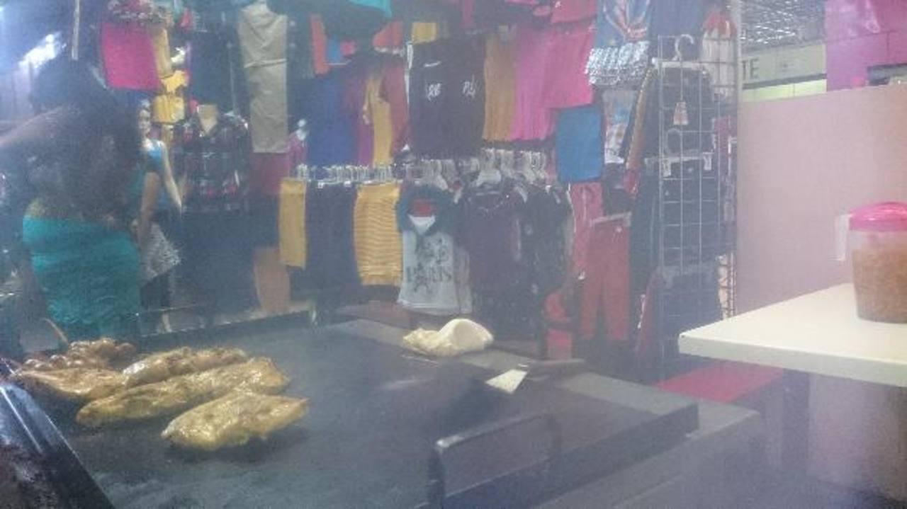 Las planchas donde cocinan los alimentos se encuentran a pocos pasos de algunos puestos donde venden ropa. fotos edh
