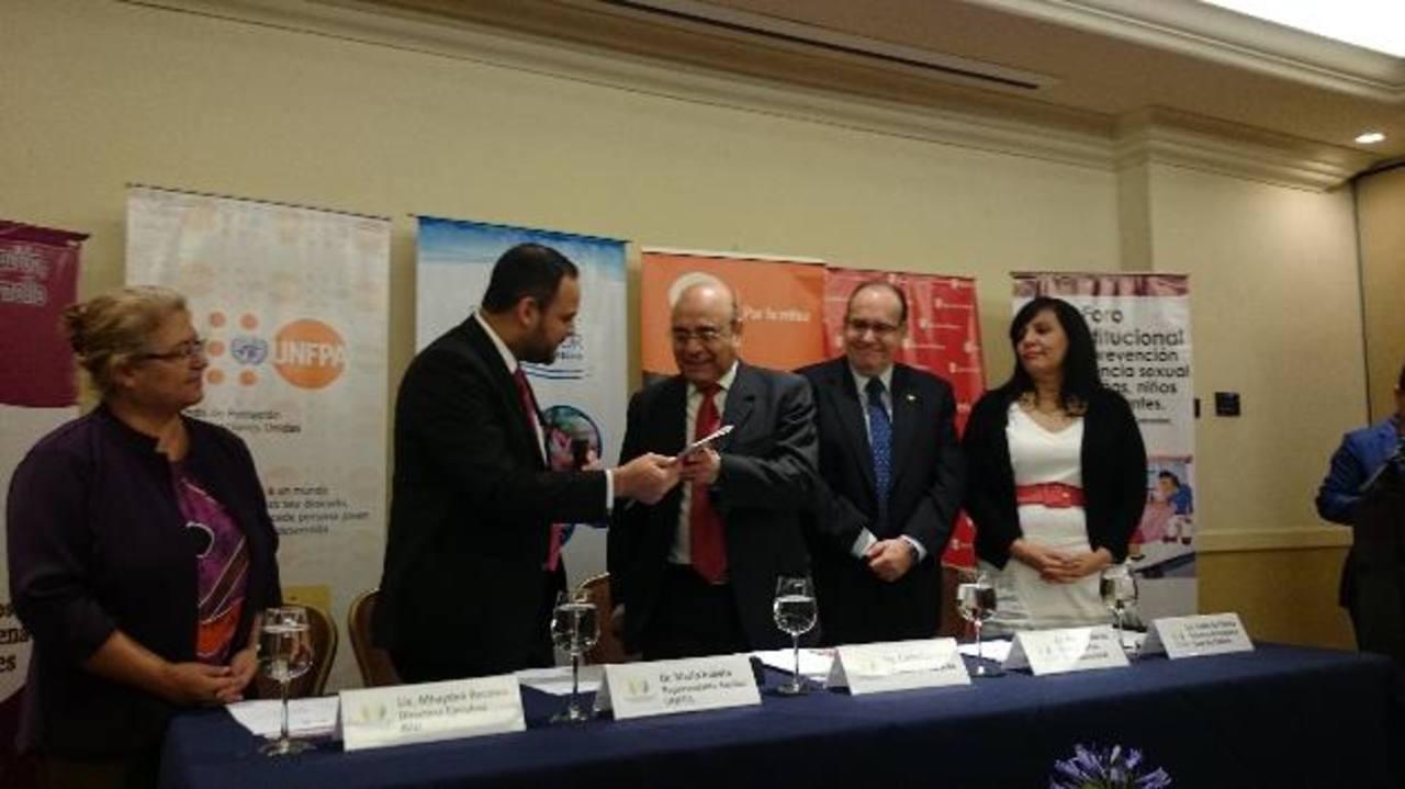 Mario Iraheta del Unfpa entregó al Ministro Carlos Canjura un protocolo para prevenir el acoso sexual. Foto EDH / Susana Joma