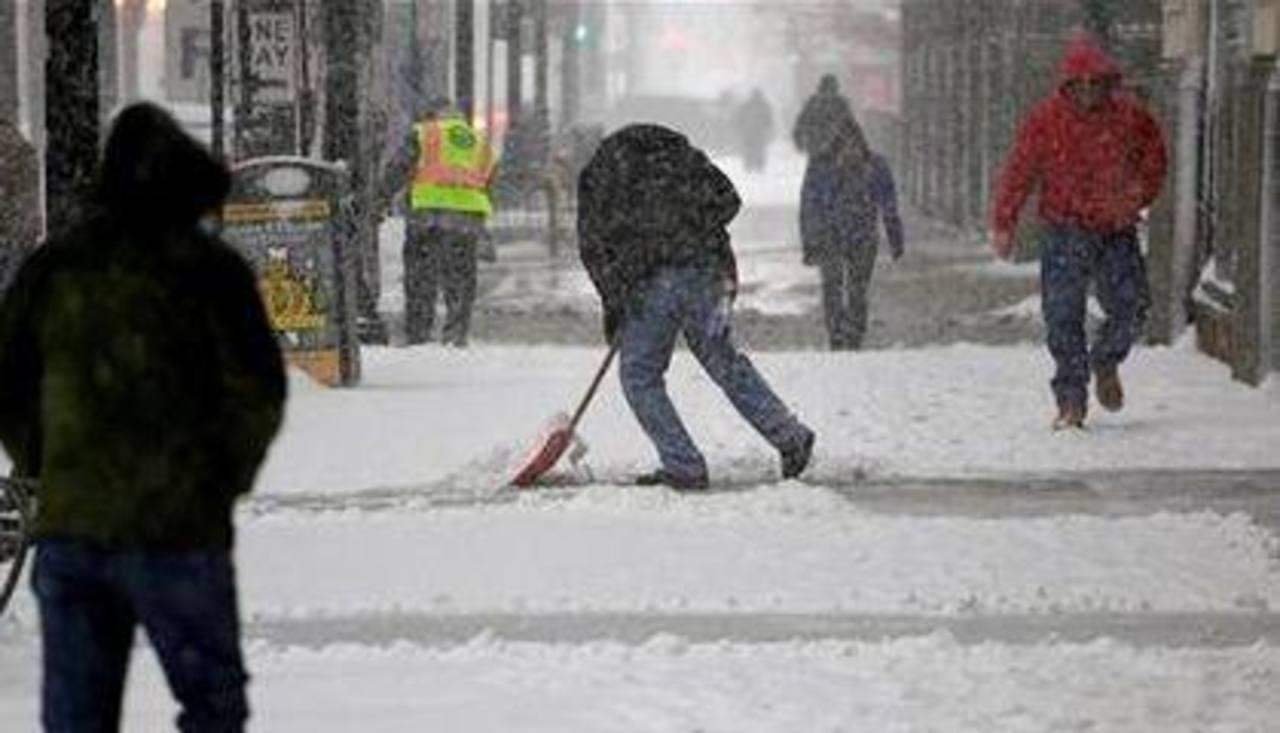 Peatones ayudan a despejar la nieve de las calles en Chicago.