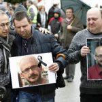 Trabajadores de la multinacional Delphi, dos de cuyos empleados viajaban en el avión siniestrado en Francia, muestran fotografías de sus compañeros muertos.