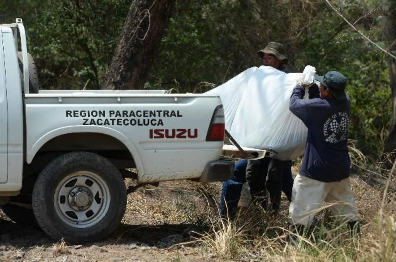 Arístides, de espaldas, ayuda a cargar el cadáver de su hijo al pick up de Medicina Legal.