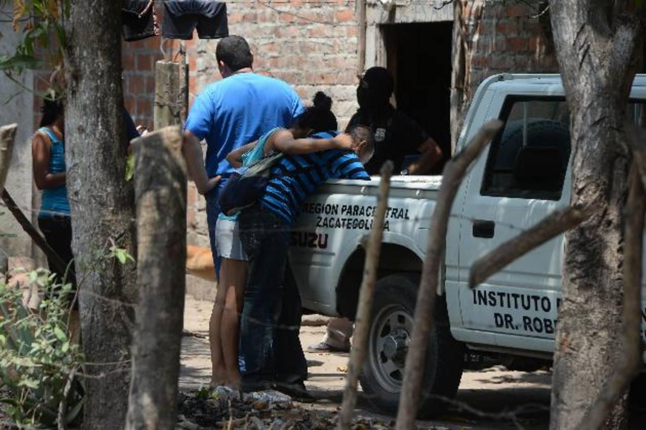 El padre del soldado Eduardo Villalta Quintanilla, de 21 años, llora sobre el cadáver de su hijo. El joven entró al Ejército para ayudar al sostenimiento de su familia. Foto EDH / Jaime Anaya.