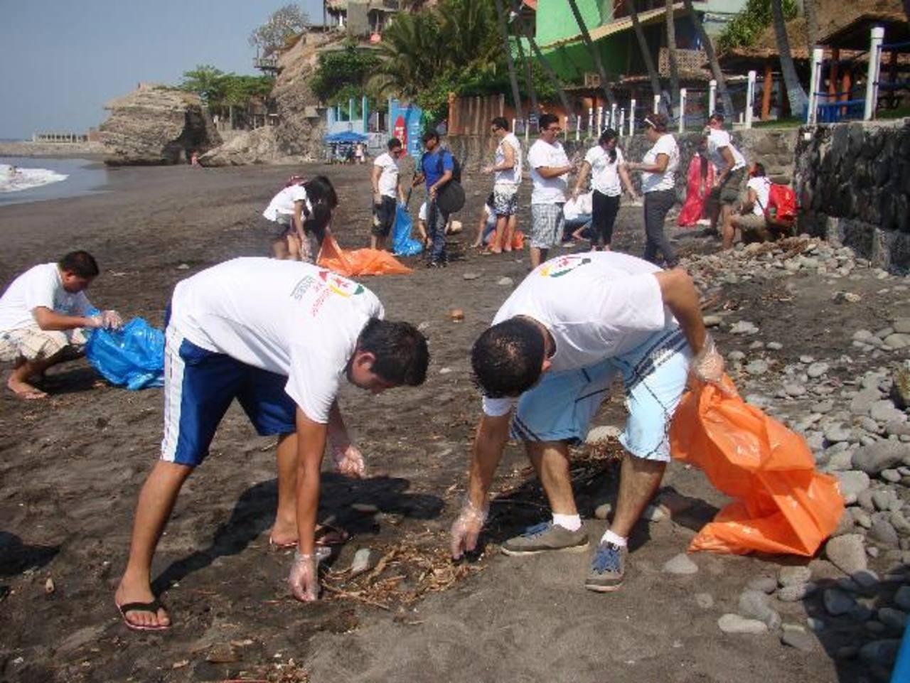 Voluntarios de Sykes realizan labores del limpieza en playa El Tunco. Fotos EDH / Cortesía