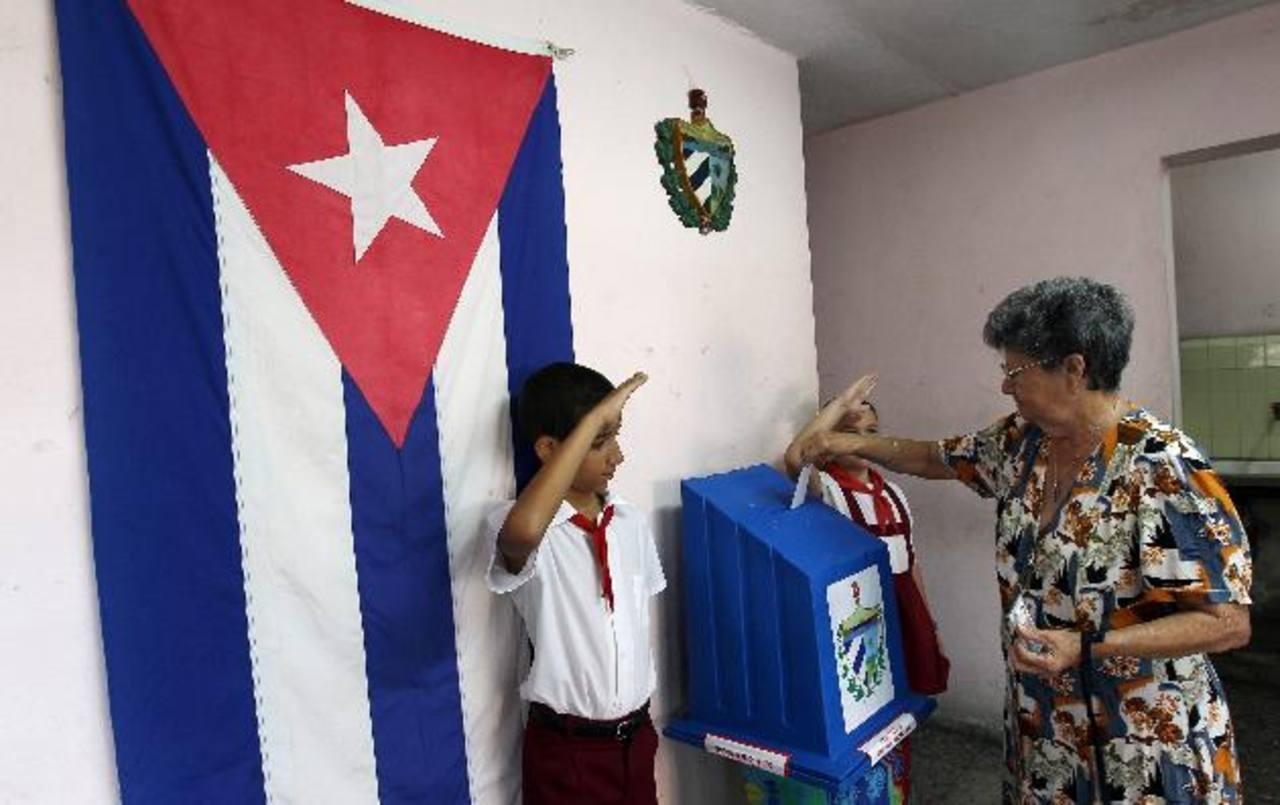 Una mujer vota mientras niños custodian las urnas, durante las elecciones de concejales.
