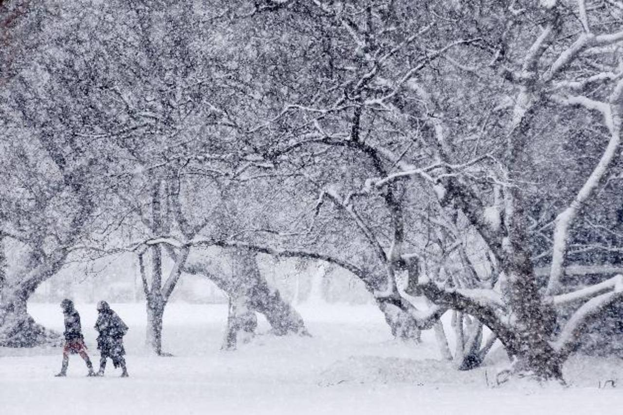 Dos personas caminan bajo una intensa nevada en los alrededores del Capitolio, en Washington DC. foto edh /efe