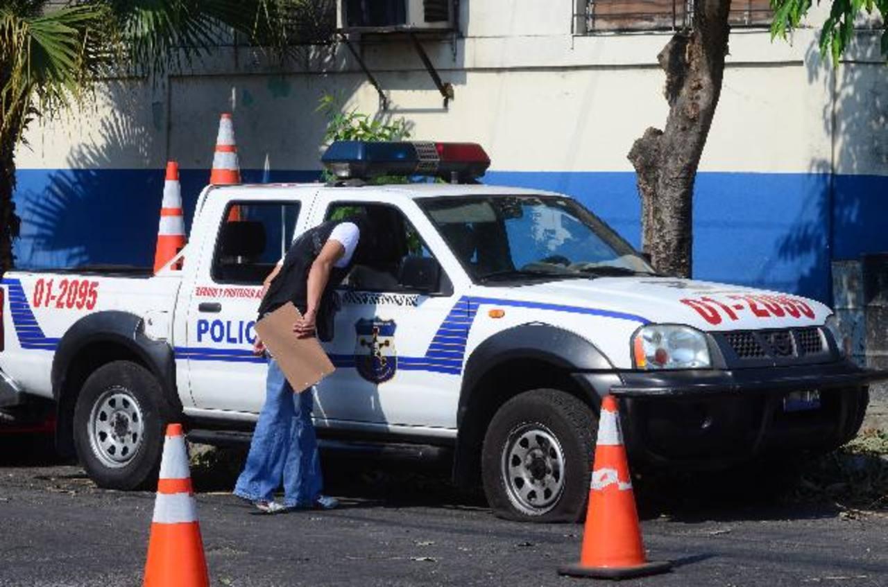 Un investigador revisa el vehículo dañado al ser atacada una sede policial sobre la 11a. Calle Oriente. Sin víctimas.
