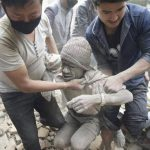 Dos hombres ayudan a otro a salir de entre los escombros donde había quedado soterrado en Katmandú tras el terremoto en Nepal. foto edh /EFE