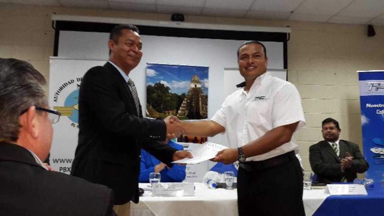 El presidente de la Autoridad de Aviación Civil, René López, (izquierda) entrega la autorización al gerente general de Transporte Aéreos de Guatemala, Javier Arango. Foto EDH/ Rodolfo Ortiz