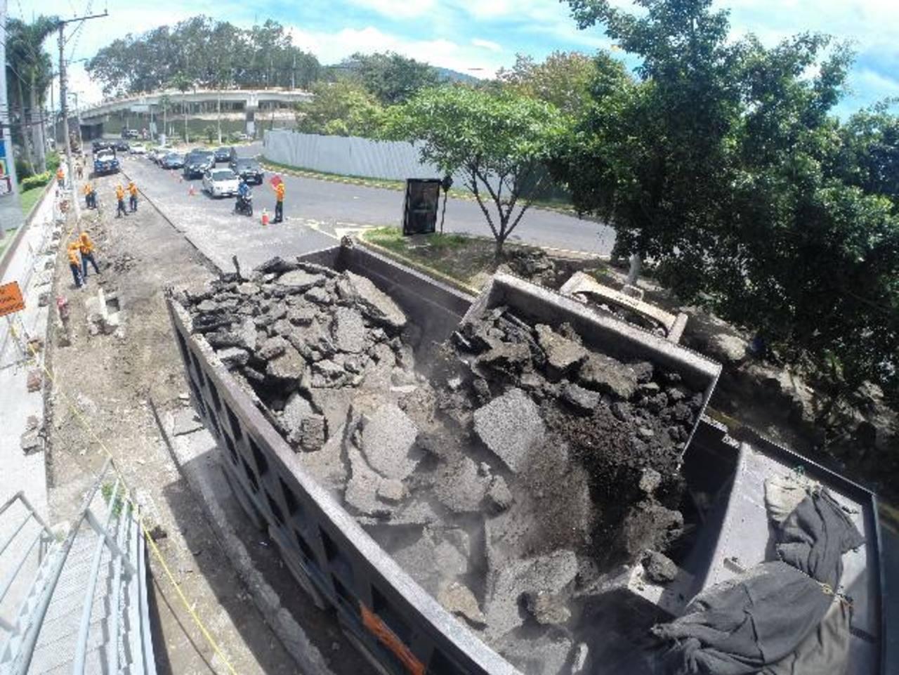 Cuadrillas de trabajadores retiran la carpeta asfáltica en el área donde se desarrolla el proyecto. Foto EDH / Mauricio castro