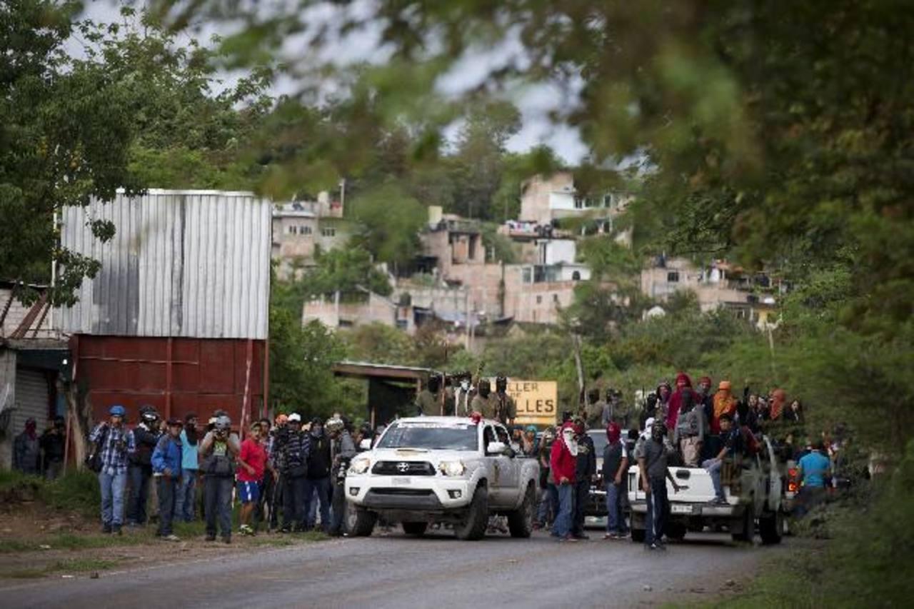 Policías comunitarios y familiares de los 43 desaparecidos retroceden tras ser recibidos con pedradas en Tixtla. foto edh / ap