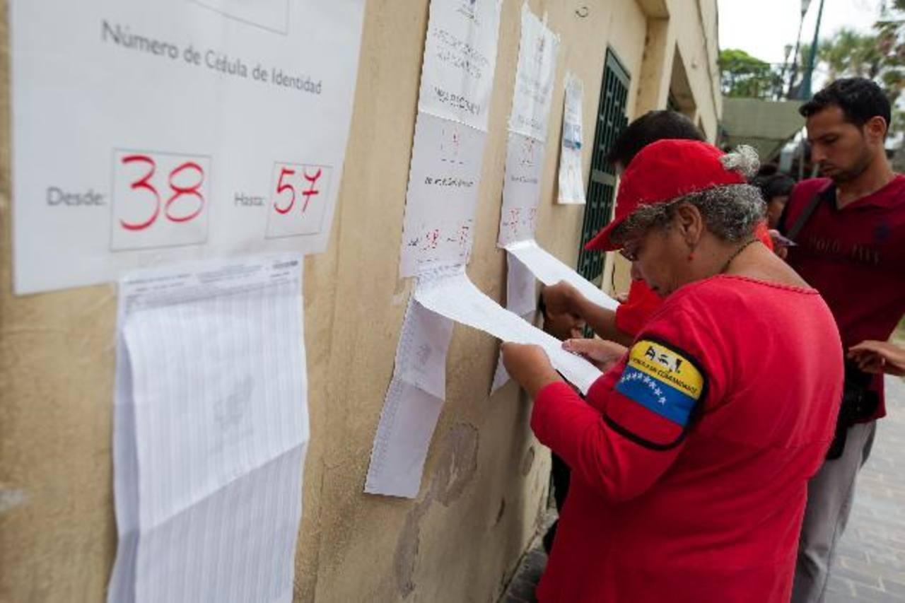 Una mujer busca la mesa de votación donde ejercerá su sufragio en un colegio del oeste de Caracas. foto edh / efe