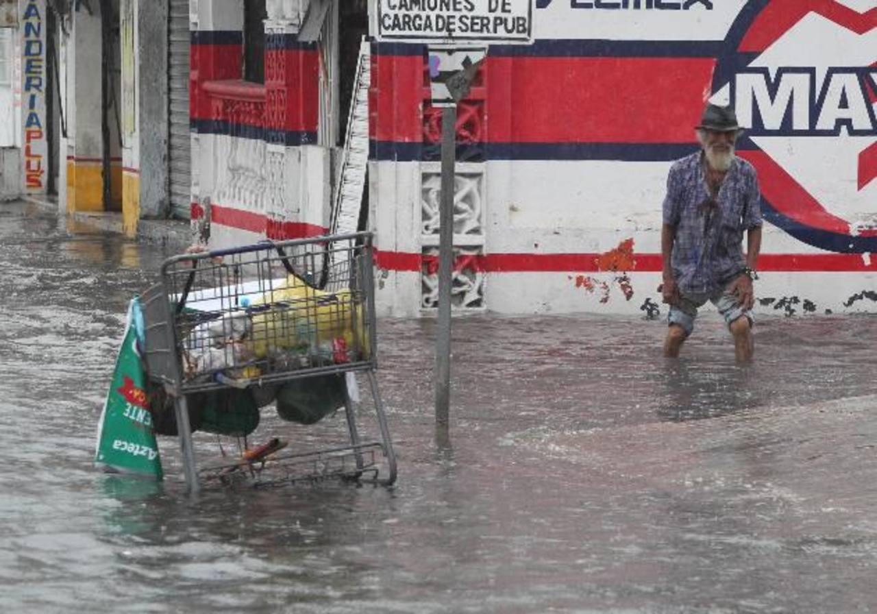 Un hombre camina por una calle inundada el 13 de junio de 2015, en Cancún, estado de Quintana Roo, México.