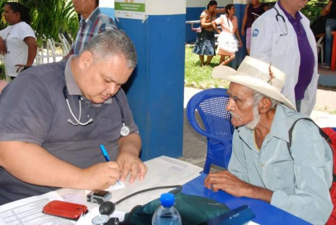 Un médico voluntario receta medicamentos a uno de los beneficiados con la asistencia de salud. Foto EDH / insy mendoza