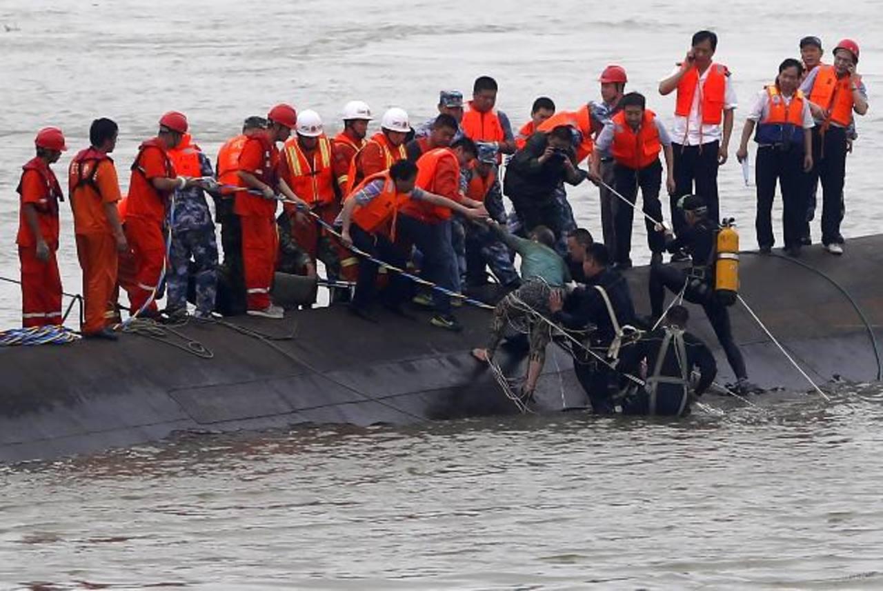 Miembros de los servicios de rescate ayudan a un sobreviviente tras el naufragio de un barco en el río Yangtsé en Jianli, China.