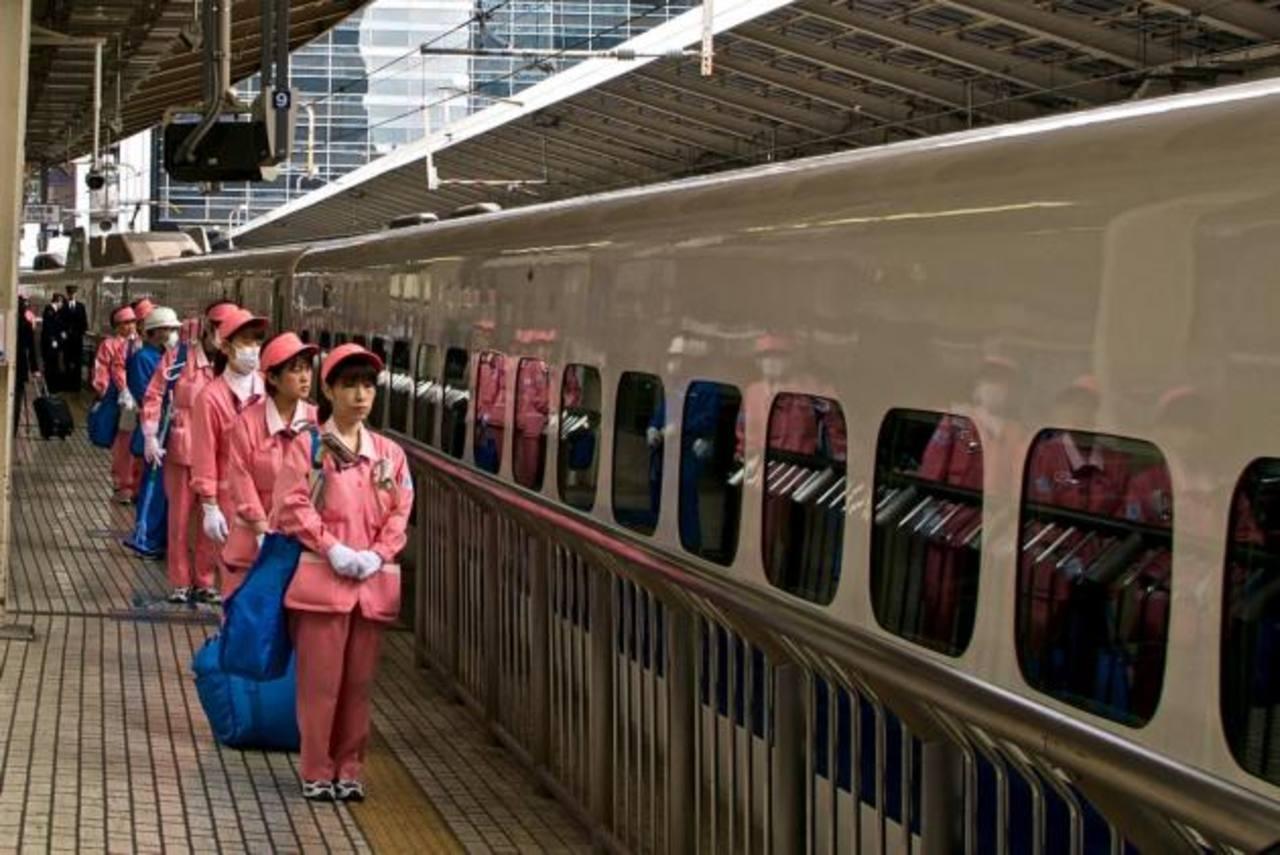 El personal de limpieza espera la llegada del Shinkansen.
