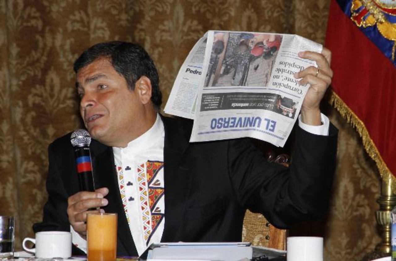 Rafael Correa sostiene un ejemplar de El Universo durante un encuentro con medios extranjeros en Quito en 2011. edh/Archivo