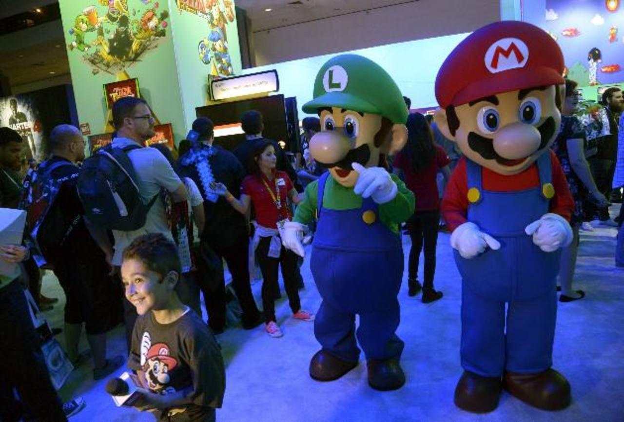 Promotores disfrazados de los personajes del videojuego de Mario Bros en la feria E3. foto/ eFE