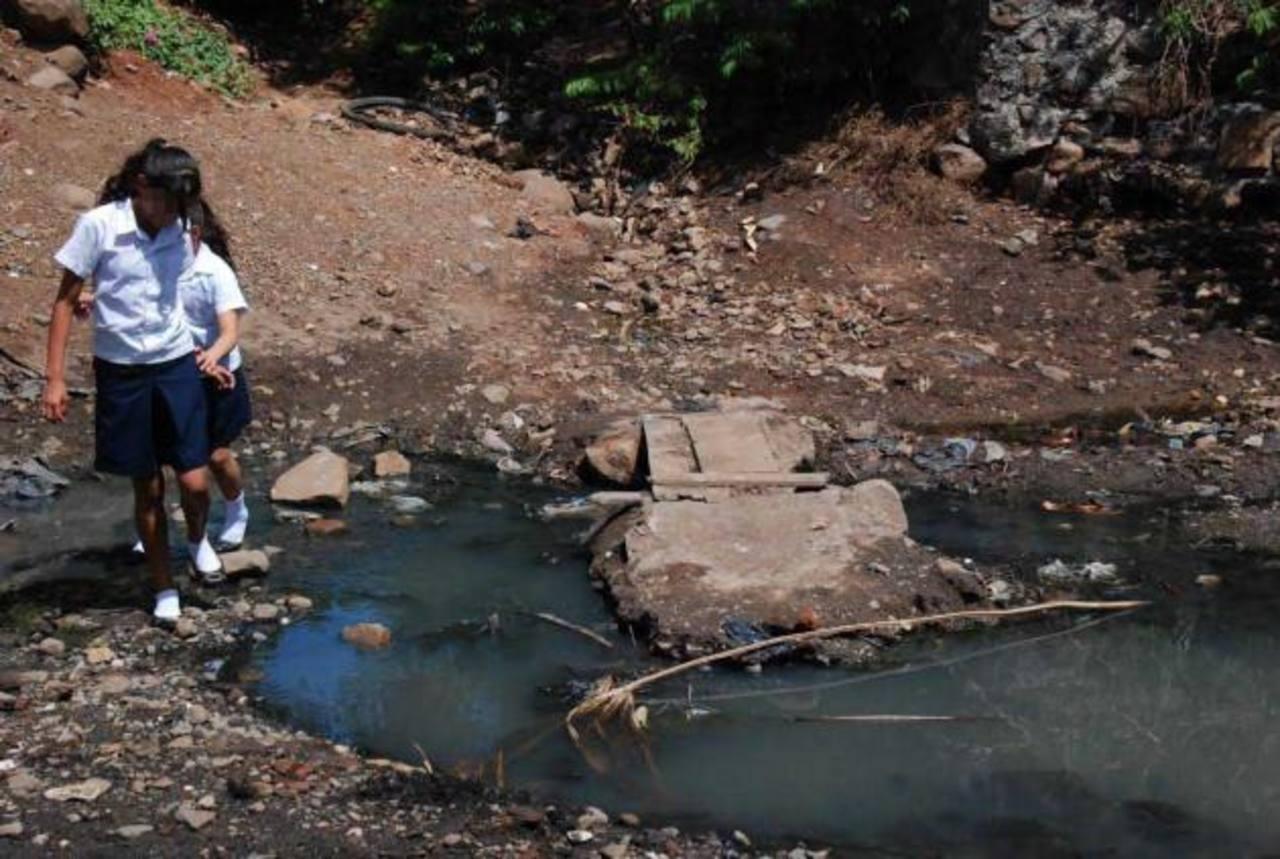 Los niños y adultos deben tener mucho equilibrio para usar las piedras y cruzar la quebrada. Foto EDH / Insy Mendoza