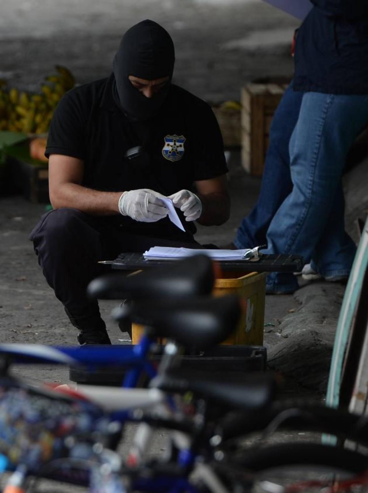 Un investigador recaba evidencias en donde fue ultimado uno de los supuestos pandilleros, en Mejicanos. Foto EDH / Jaime Anaya