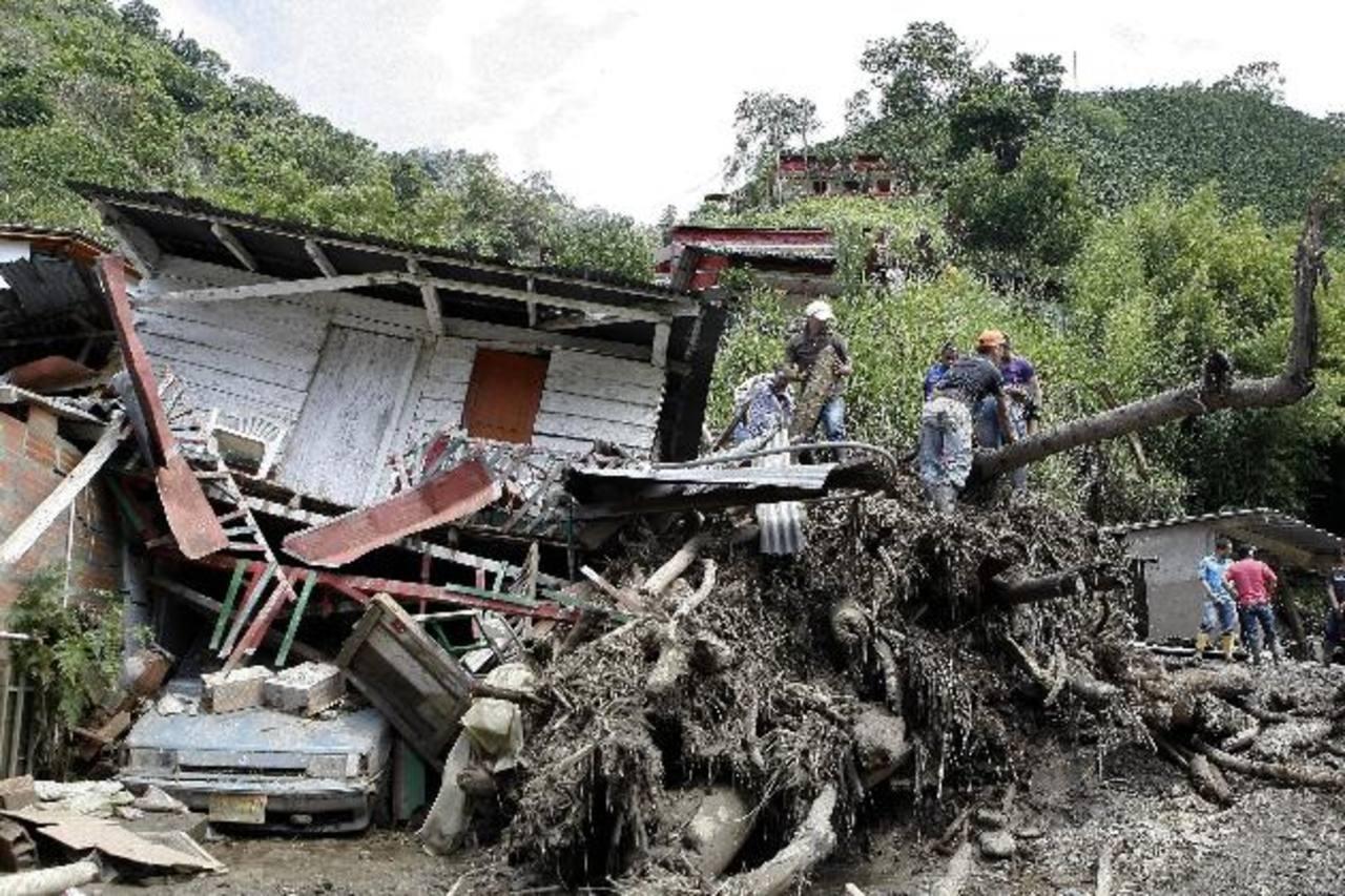 Habitantes y rescatistas buscan cuerpos de víctimas de una riada ocasionada por una quebrada. foto edh / efeUn hombre observa su casa, que fue destruida por el alud en Salgar, Antioquia. foto edh / ap