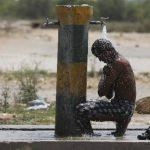 Un trabajador indio se refresca bajo un grifo una calurosa tarde en Amritsar.