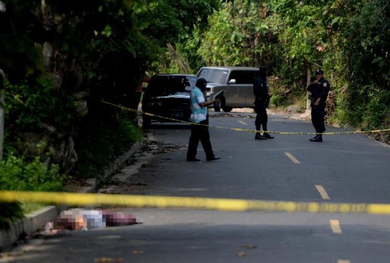 El cadáver de un hombre que tenía tatuajes alusivos a una pandilla fue abandonado ayer frente a una residencial de Quezaltepeque. Foto EDH / Marlon Hernández