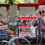 Conductores de bici-taxis duermen en sus transportes en un día de fuerte calor en Nueva Delhi, India.