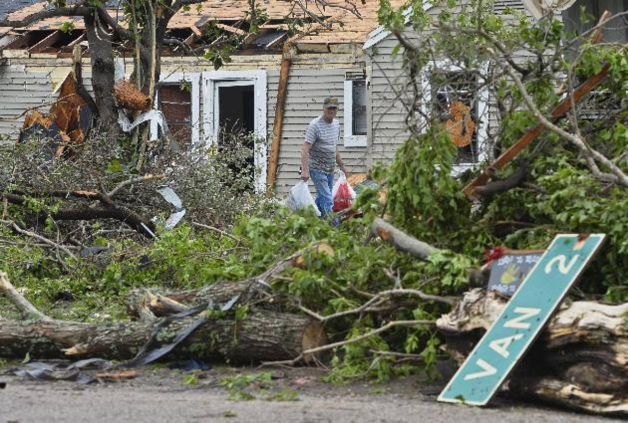 Un hombre recoge objetos de su casa, destruída tras el fuerte tornado. foto edh /EFE