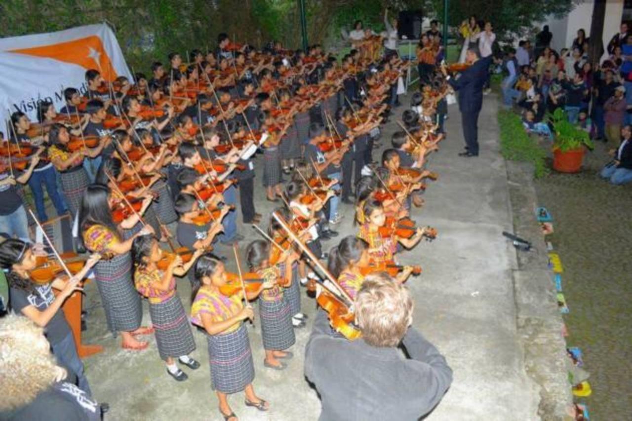 El Director de Orquesta Forma Acústica, Julio César Rodríguez (al fondo), dirigiendo un concierto en Guatemala. foto CORTESÍA