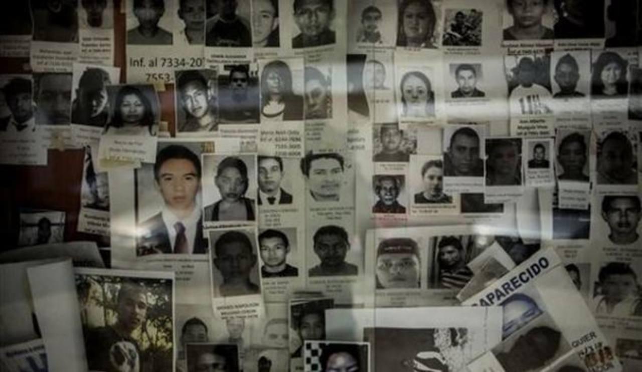 Fotografías de personas desaparecidas clavadas a una pared en el Instituto de Medicina Legal en San Salvador