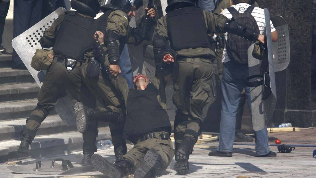 Police officers carry their injured colleague after grenade exploded