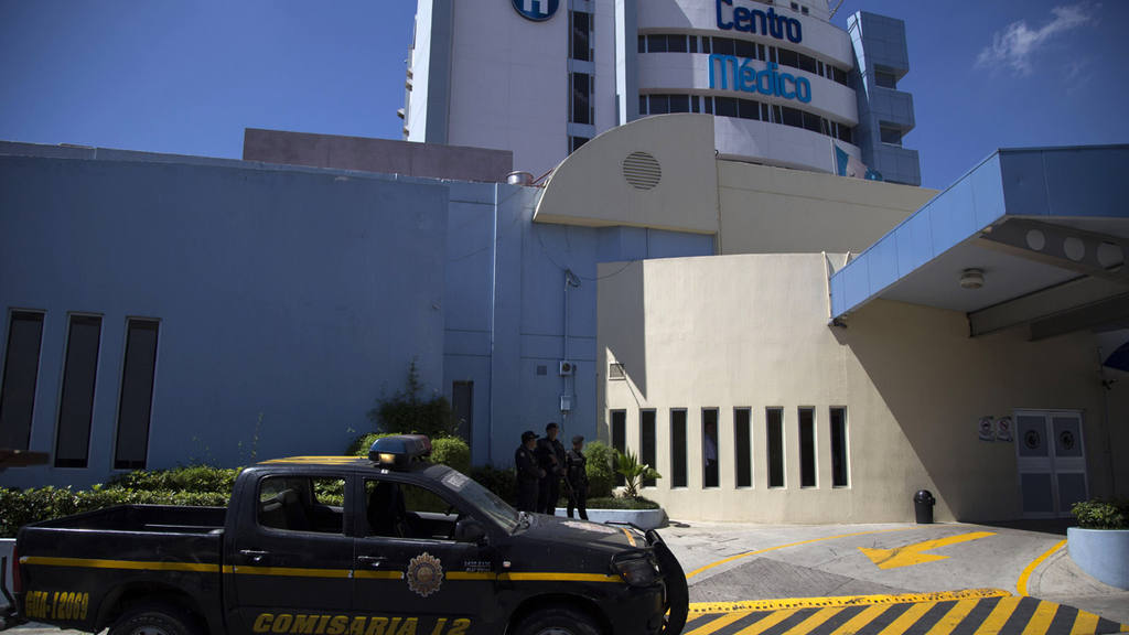 Police stand guard outside a private hospital where Guatemala's forme