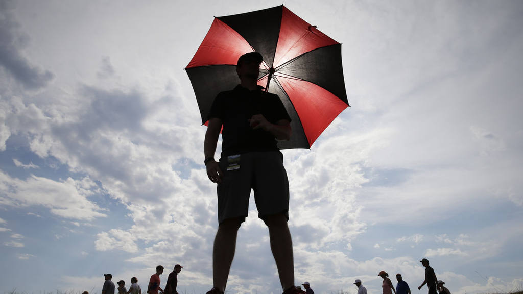 A fan uses an umbrella for shade near the seventh hole during the sec