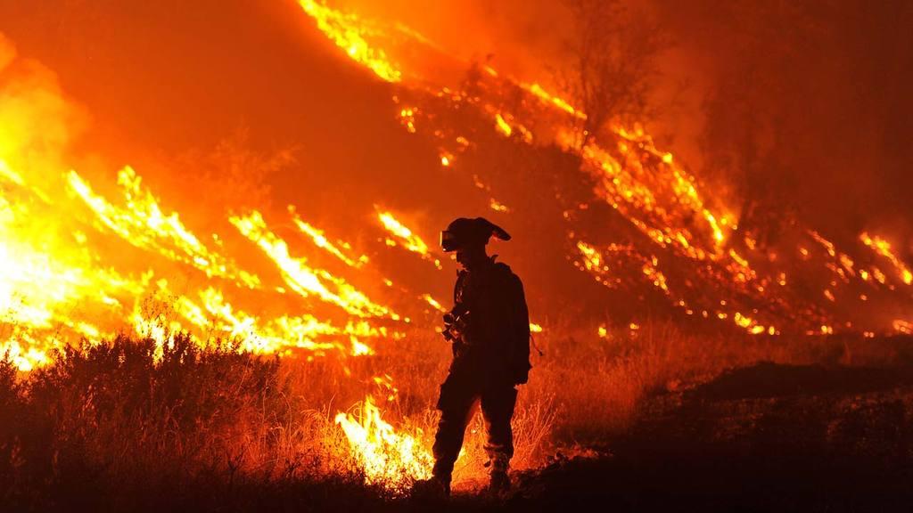 CalFire firefighter Bo Santiago lights a backfire as the Rocky fire b