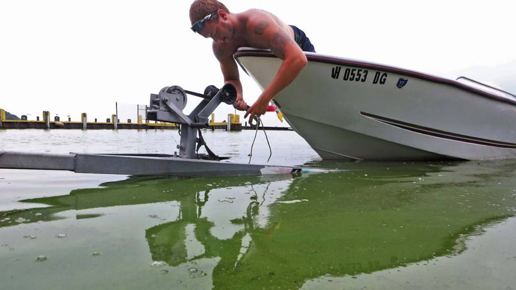 Ryan Atkins who works at a boat rental helps bring a boat ashore at