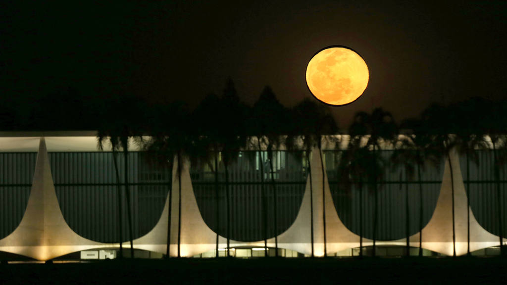 A full moon rises behind the Alvorada Palace