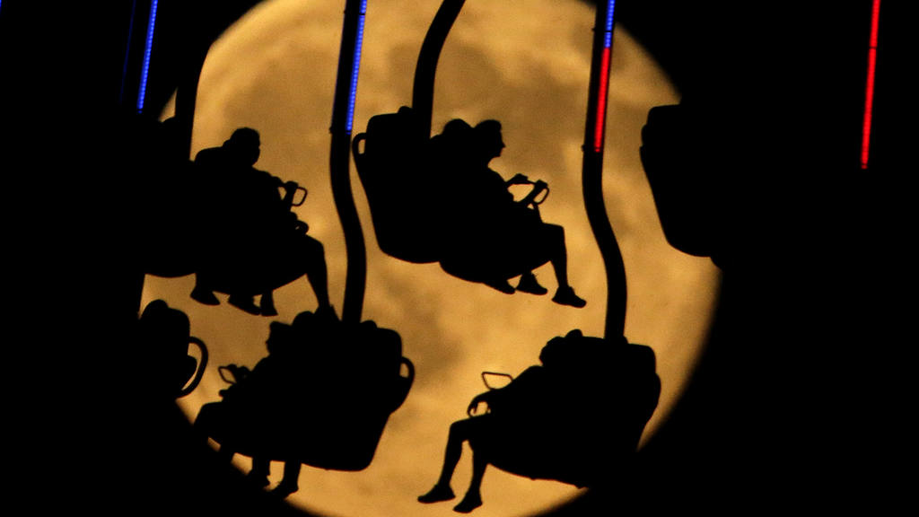 People are silhouetted against a rising blue moon as they ride an att