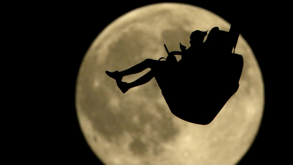A girl is silhouetted against a rising full moon as she ride an attra