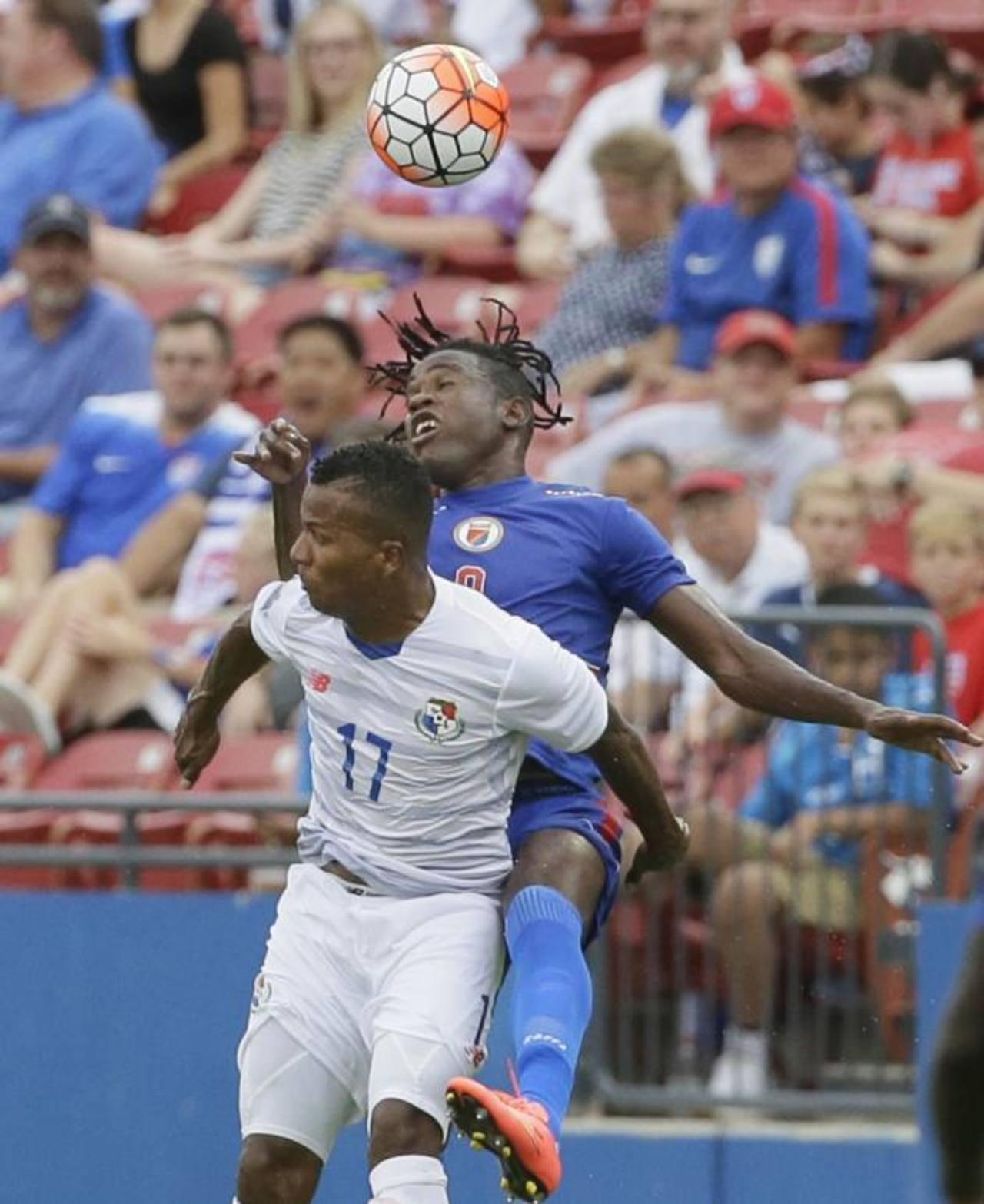 El atacante haitiano Kervens Belfort (de azul) lucha en el aire contra el zaguero panameño Luis Henríquez. Foto EDH/ AP