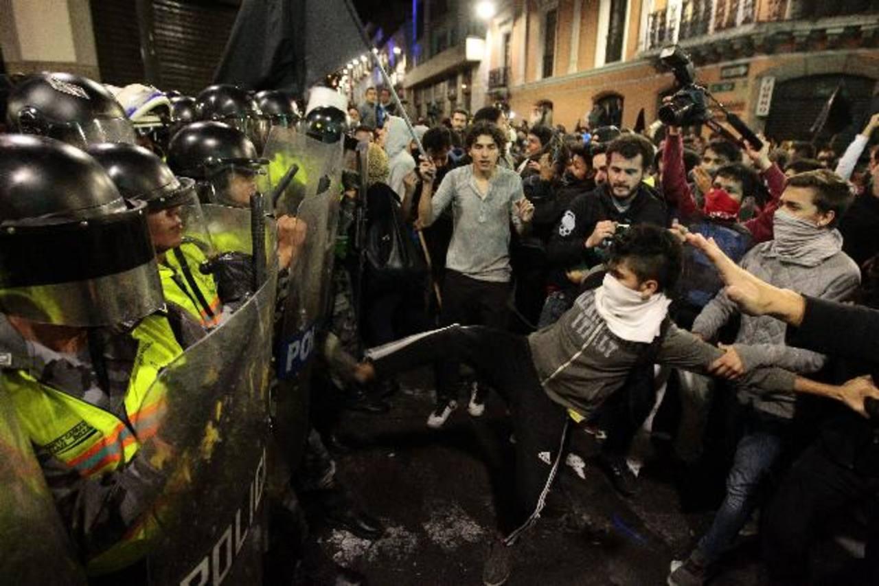 Manifestantes se enfrentan a la Policía durante una marcha contra la gestión del gobernante ecuatoriano, Rafael Correa, el pasado 26 de junio, en Quito. foto edh / efe
