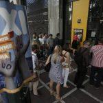 Un grupo de personas espera para poder sacar dinero junto a un cartel que apoya en 'no' en el referéndum en una sucursal del un banco en Atenas.