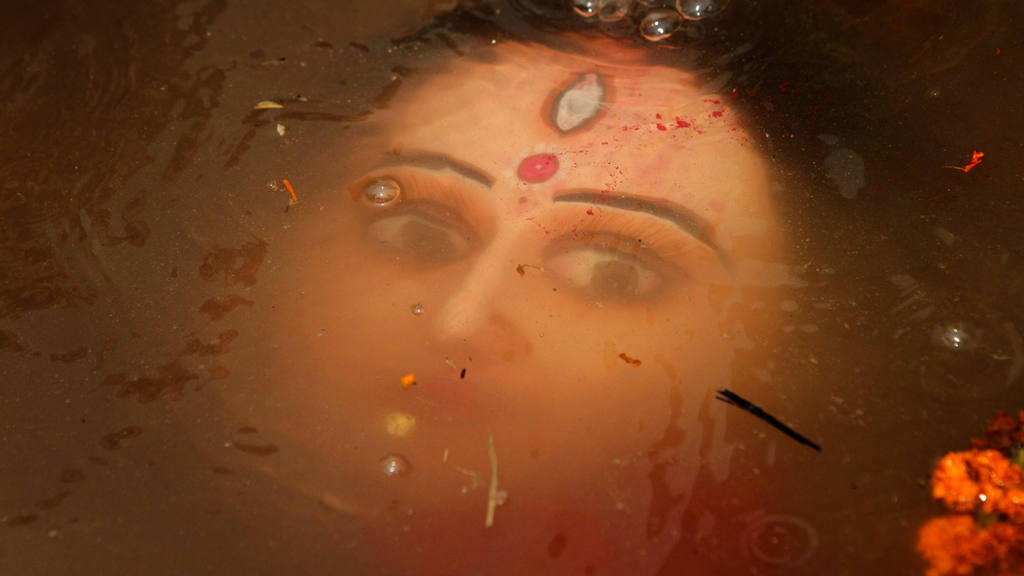 An idol of Hindu goddess Durga floats in water as devotees immerse th