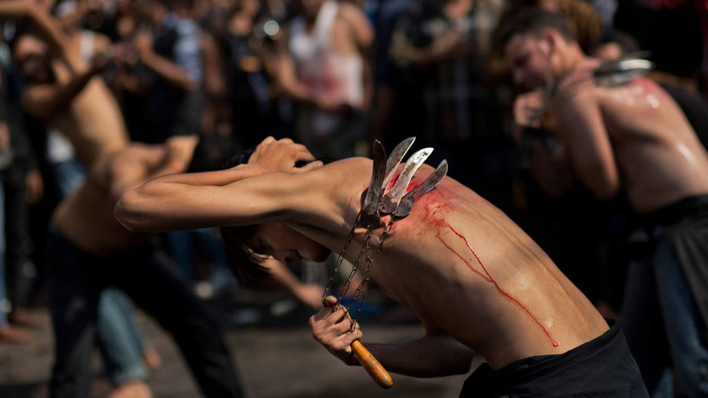 An Indian Shiite Muslim flagellates himself during a procession to ma